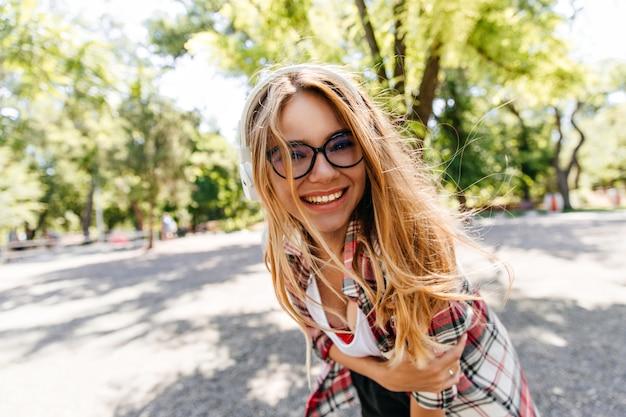 Fascinante garota com cabelo comprido, passando um tempo no parque. na moda senhora caucasiana rindo durante o verão ao ar livre.