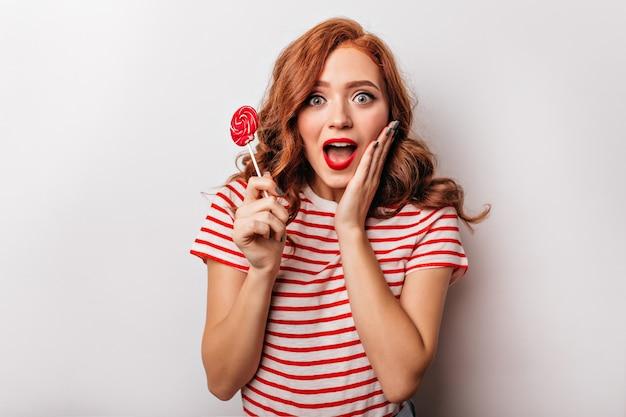 Fascinante garota ruiva posando na parede branca com um sorriso surpreso. elegante mulher encaracolada com pirulito.