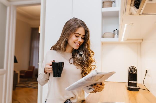Fascinante modelo feminina com cabelo castanho claro lendo diário na cozinha