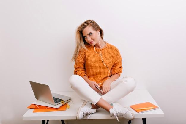 Fascinante mulher loira em tênis esportivos sentada na mesa e olhando com um sorriso divertido depois do trabalho com o laptop