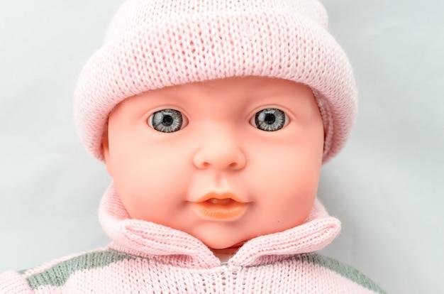 Fase de boneca bebê fofo em vestido de malha close-up