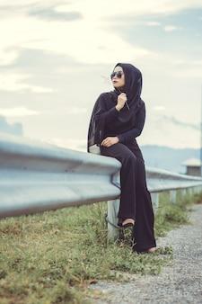 Fashi retrato de uma jovem mulher muçulmana bonita com o hijab preto e vestido preto completo. estilo vintage