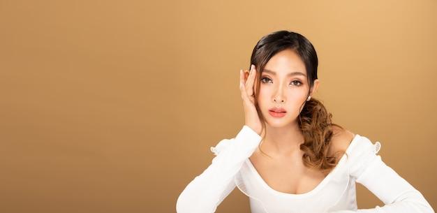Fashion beauty woman tem longos cabelos loiros negros e expressa o sentimento de felicidade. retrato de menina asiática usando vestido branco sobre parede de tom amarelo, copie o espaço