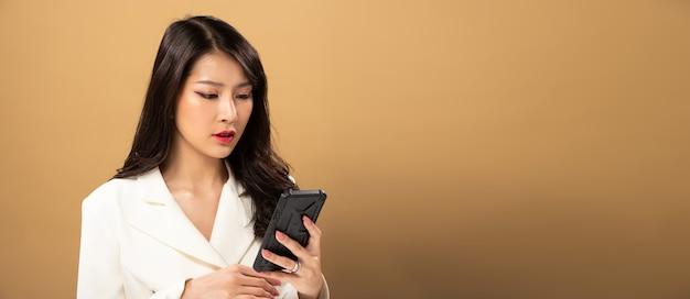 Fashion beauty woman tem longos cabelos negros e expressa o sentimento de felicidade. retrato de menina asiática usando um vestido branco e usando o bate-papo por telefone inteligente na parede amarela, copie o espaço