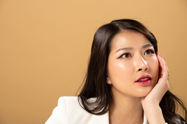 Fashion beauty woman tem longos cabelos negros e expressa o sentimento de felicidade. retrato de menina asiática usando vestido branco sobre parede de tom amarelo, copie o espaço