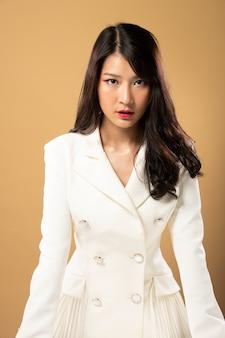 Fashion beauty woman tem longos cabelos negros e expressa o sentimento de felicidade. retrato de menina asiática usando vestido branco sobre parede de tom amarelo
