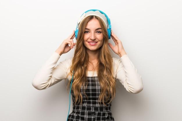 Fashionably mulher usando chapéu ouvindo música com fones de ouvido