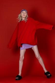 Fashionista glamourosa em roupas esportivas posando dinamicamente sobre o fundo vermelho