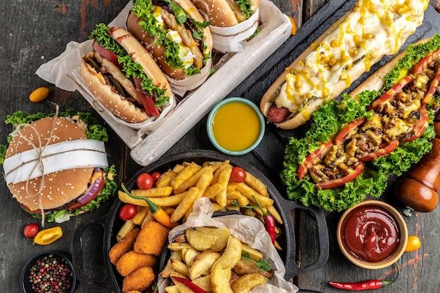 Fast food americano. hambúrgueres, batatas fritas, cachorros-quentes. fast food e o conceito de alimentação pouco saudável. vista do topo