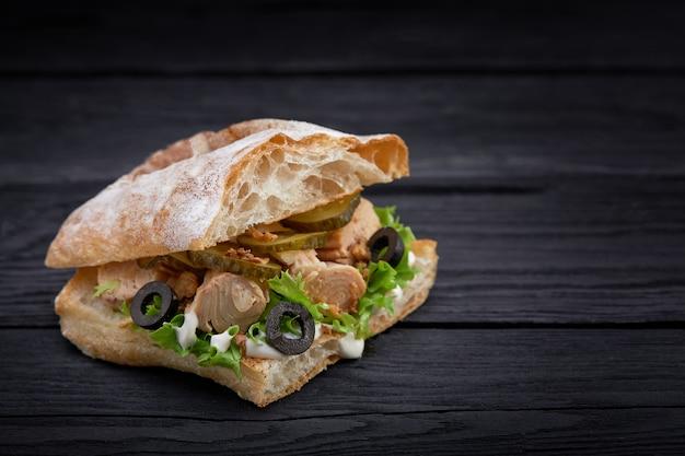 Fast-food americano. sanduíche de atum suculento com queijo, salada e azeitonas em um fundo escuro. comida do clube.