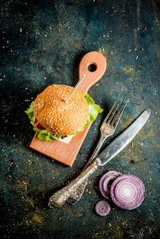 Fast-food comida não saudável deliciosos hambúrgueres saborosos frescos com costeleta de carne legumes frescos e queijo em fundo de concreto azul escuro