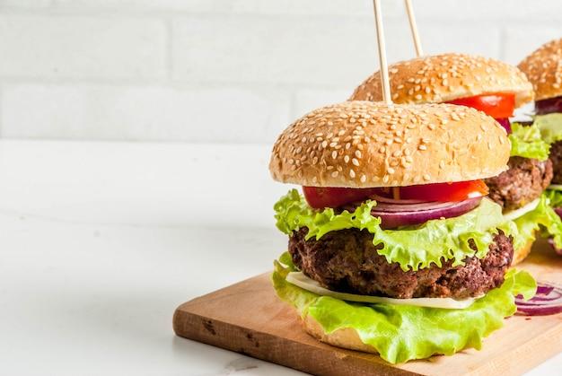 Fast food comida não saudável deliciosos hambúrgueres saborosos frescos com costeleta de carne legumes frescos e queijo no fundo branco