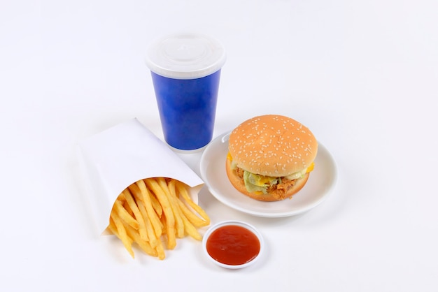 Fast food conjunto contendo hambúrgueres, batatas fritas e refrigerante, isolado no fundo branco.