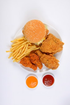 Fast food conjunto contendo hambúrgueres, frango frito e batatas fritas isoladas no branco backgro