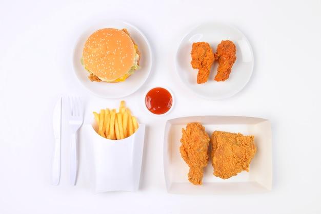 Fast food conjunto contendo hambúrgueres, frango frito e batatas fritas, isolado no fundo branco.