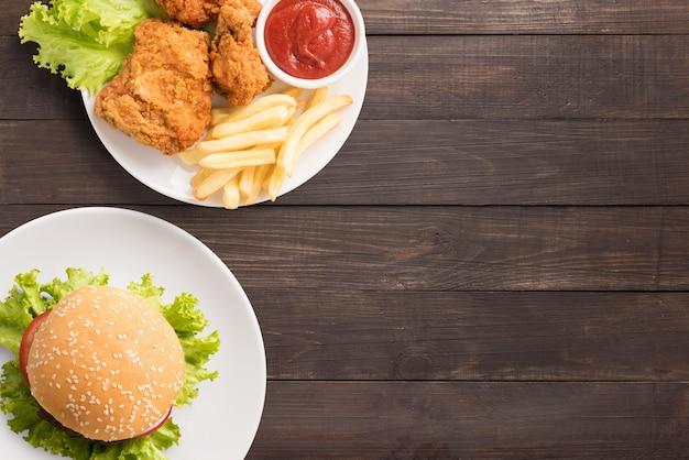 Fast-food conjunto frango frito, batata frita e hambúrguer em fundo de madeira