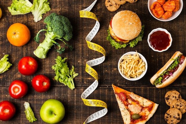 Fast food e legumes na mesa de madeira