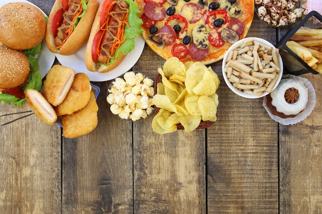 Fast-food em fundo de madeira velho. conceito de junk eating. vista do topo. postura plana.