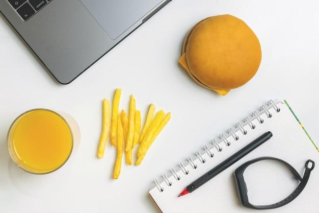 Fast food no trabalho petiscar. laptop, hambúrguer, batata frita e rastreador de aptidão no local de trabalho