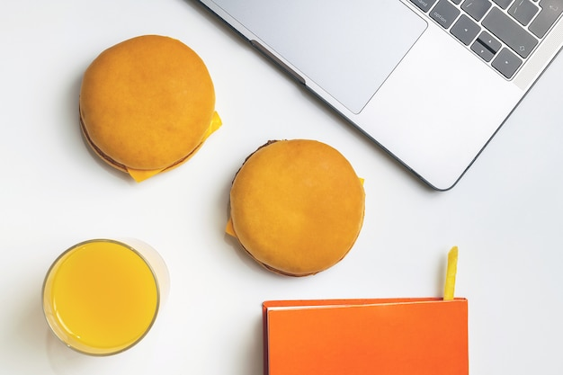 Fast food no trabalho petiscar. laptop, notebook, dois hambúrgueres e batatas fritas no local de trabalho.