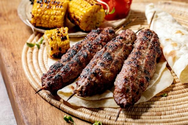 Fast food oriental. grelhado de carne picante lyulya kebab em palitos no pão achatado com vegetais grelhados espiga de milho doce, tomate e páprica, molho de tomate na mesa de madeira.