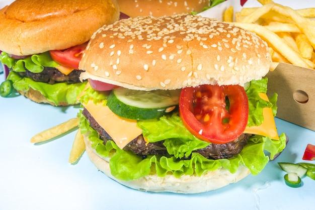 Fastfood, conceito de festa do hambúrguer. vários hambúrgueres deliciosos com batatas fritas e molhos