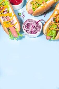 Fastfood grelhada de churrasco, vários cachorros-quentes tradicionais americanos com salsicha, mostarda amarela, ketchup e salada de legumes frescos, vista de cima em fundo azul brilhante com batatas fritas