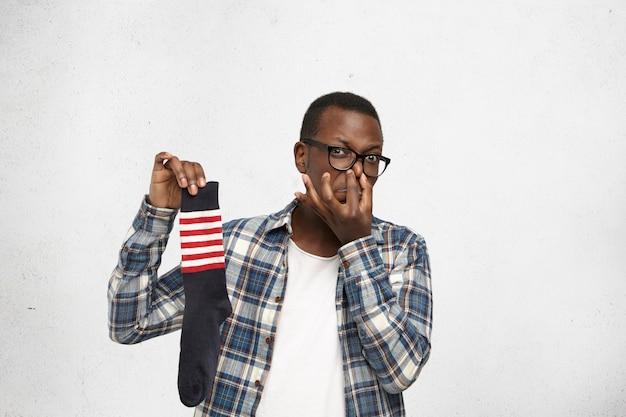 Fastidious jovem afro-americano vestindo óculos e camisa sobre camiseta branca, segurando a meia suada e fedida na mão e beliscando o nariz, seu olhar expressando desgosto com um cheiro desagradável