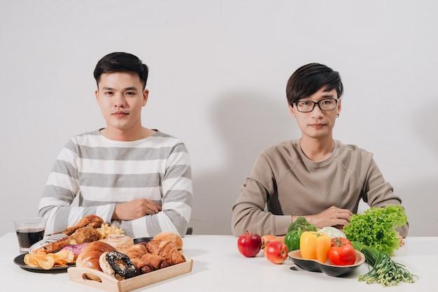 Fat chateado com bandejas com comida na mesa branca. conceito de estilo de vida saudável. homem sentado. dois homens. bandeja com hambúrgueres. homem com excesso de peso. alimentação saudável e vegetariana.