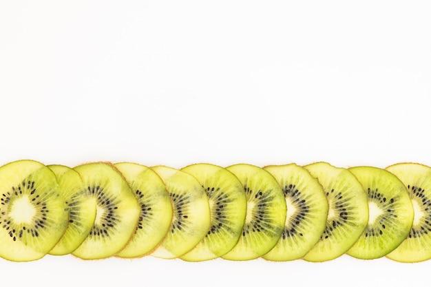 Fatia da fruta de quivi como o teste padrão põr sobre o branco.
