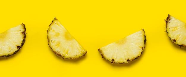 Fatia de abacaxi contra um fundo amarelo. vista superior, configuração plana. bandeira.