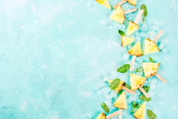 Fatia de abacaxi palitos de picolé e folhas de hortelã sobre fundo azul claro com gelo verão conceito plana leigos