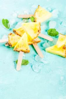 Fatia de abacaxi palitos de picolé e folhas de hortelã sobre fundo azul claro com o conceito de verão gelo