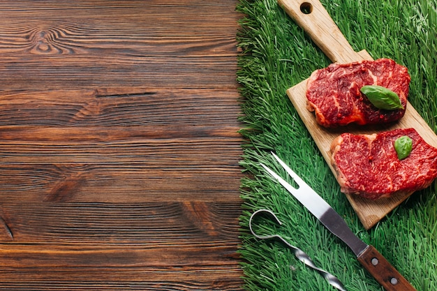 Fatia de bife cru na tábua de madeira com espeto metálico e garfo sobre tapete de grama