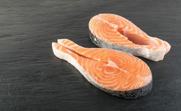 Fatia de bife de salmão rosa cru para close-up do menu do restaurante. pedaço grosso de peixe vermelho fresco, camarão ou truta