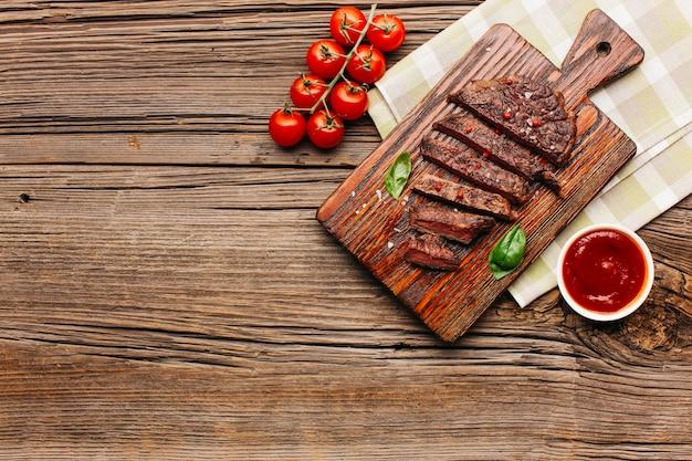 Fatia de bife grelhado na tábua e tomate sobre fundo de madeira