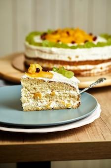 Fatia de bolo caseiro de caramelo com frutas no prato. fundo de madeira