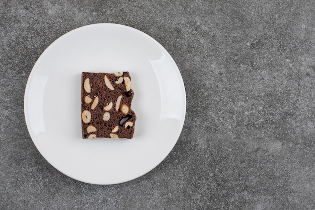 Fatia de bolo caseiro fresco na chapa branca. amendoim e chocolate.