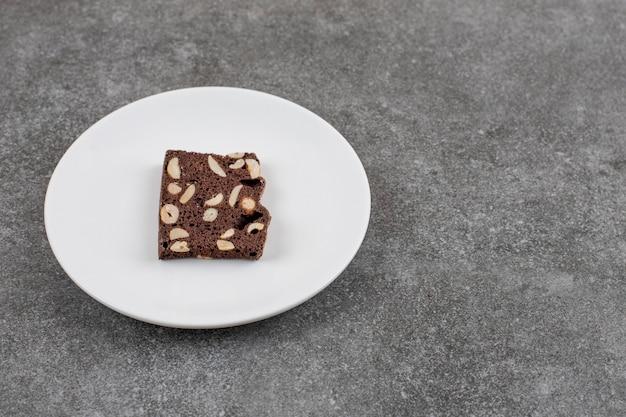 Fatia de bolo caseiro fresco no prato. bolo de chocolate com amendoim.