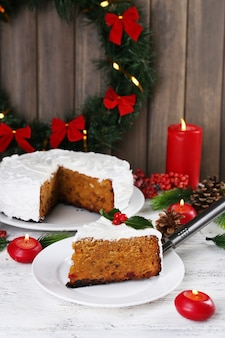 Fatia de bolo coberto de creme com decoração de natal na mesa, na parede de madeira