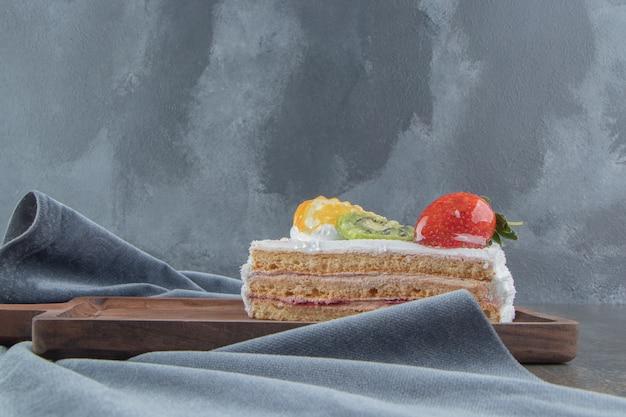 Fatia de bolo com cobertura de frutas e creme em uma pequena placa de madeira