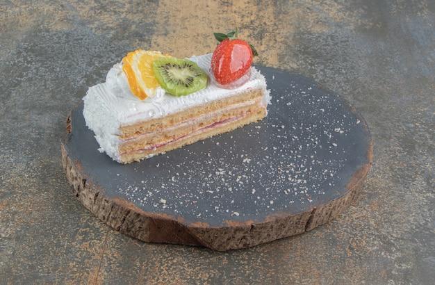 Fatia de bolo com cobertura de frutas em uma placa de madeira