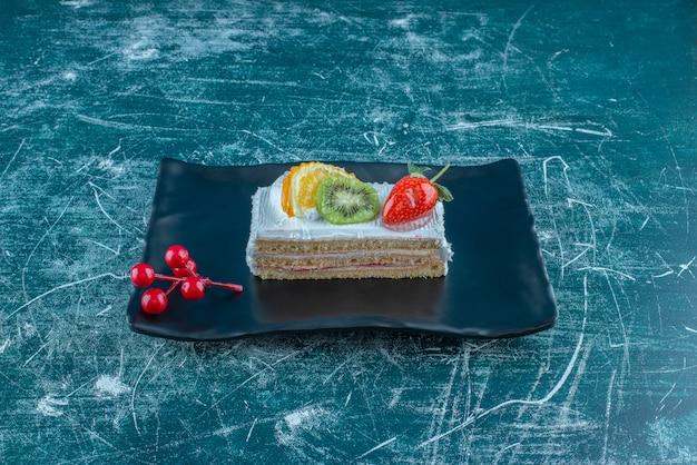 Fatia de bolo com cobertura de frutas em uma travessa sobre fundo azul. foto de alta qualidade