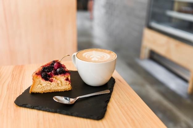 Fatia de bolo com colher e cappuccino café na placa de xisto sobre a mesa de madeira