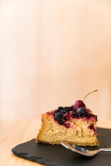 Fatia de bolo com colher na placa de xisto