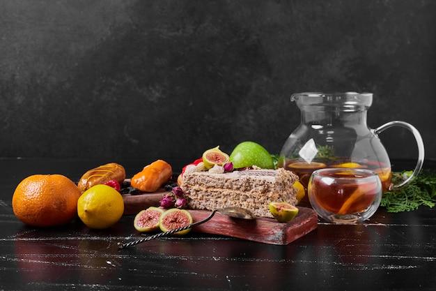 Fatia de bolo com frutas na travessa de madeira.
