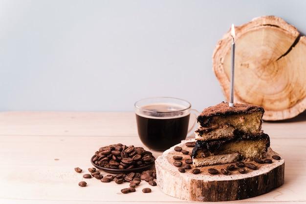 Fatia de bolo com vela e grãos de café e copie o espaço