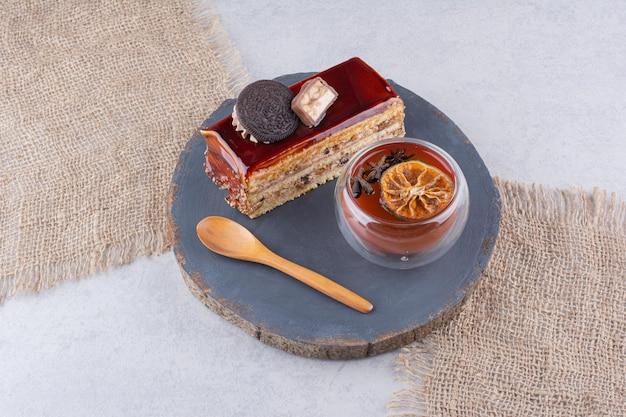 Fatia de bolo, copo de chá e colher no quadro escuro. foto de alta qualidade