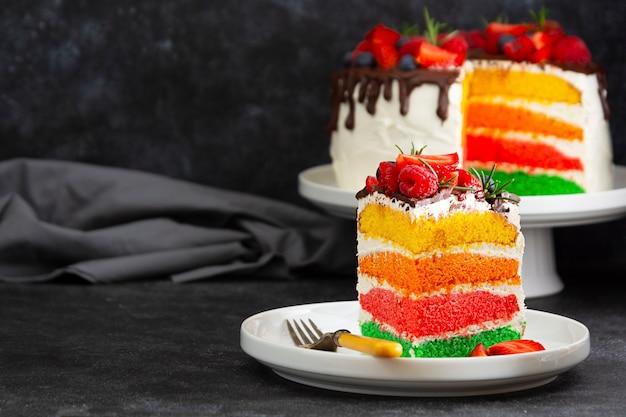 Fatia de bolo de arco-íris com frutas frescas sobre fundo escuro.