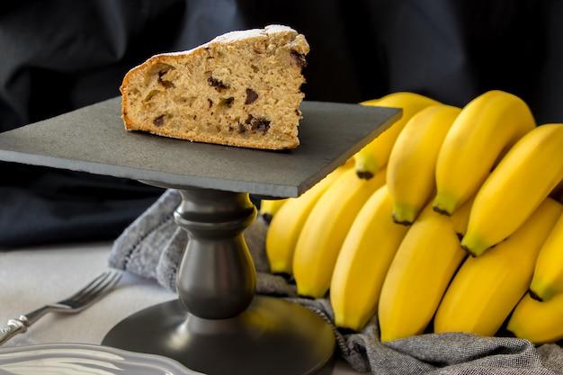 Fatia de bolo de banana caseiro ou pão na placa de ardósia preta com cacho de bananas amarelas orgânicas